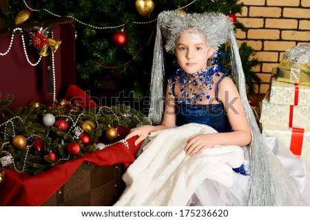 Portrait of a beautiful girl who looks like a little snow Queen. Christmas background. - stock photo