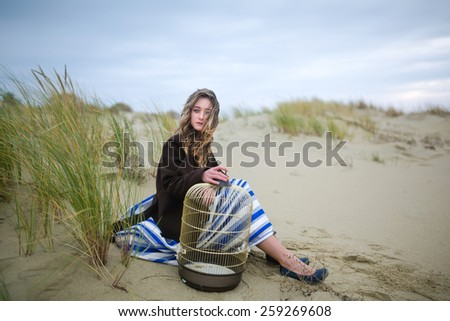 Portrait of a beautiful girl with a birdcage in a dune