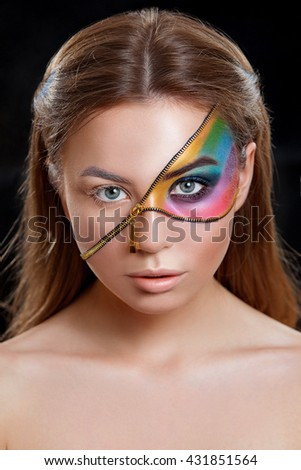 Portrait of a beautiful girl with a creative make-up , with a lock on the face and shades Radukov . Beauty clean skin . Photographed in studio on a dark background .