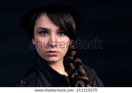 Portrait of a beautiful girl with a plait and wearing a hat.