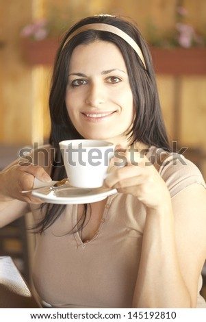 Portrait of a beautiful girl with a ribbon drinking coffee