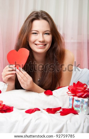 Portrait of a beautiful girl with a valentine in the hands of the bed