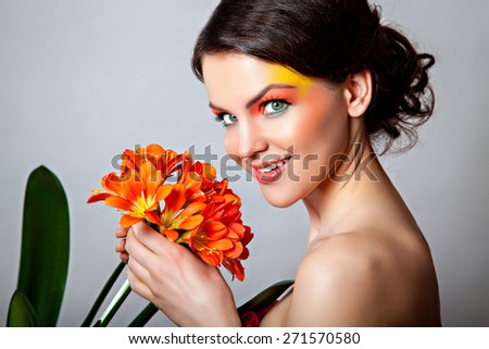 Portrait of a beautiful girl with an orange flower clivia