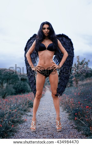 Portrait of a beautiful girl with black wings a demon in the nature of fashion style - stock photo