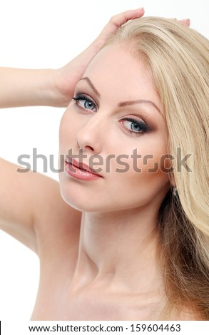 Portrait of a beautiful girl with blonde hair and naked shoulders who is posing over a white background