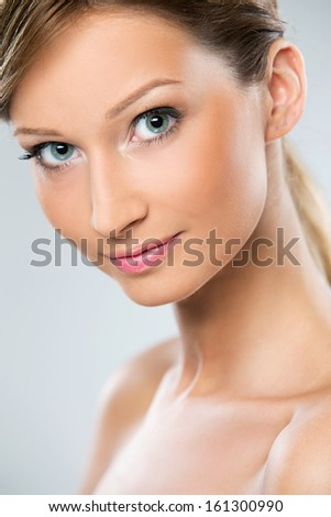 Portrait of a beautiful girl with blonde hair who is posing with her shoulders naked over a bright background