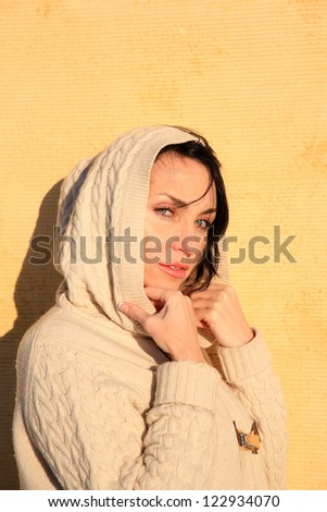 portrait of a beautiful girl with blue eyes posing on a yellow wall - stock photo