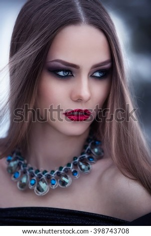 portrait of a beautiful girl with bright makeup and beautiful necklace in a winter landscape - stock photo