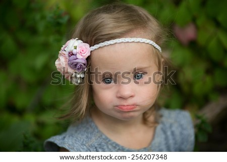 portrait of a beautiful girl with Down syndrome - stock photo