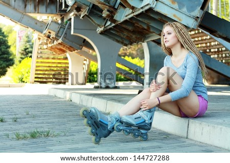 portrait of a beautiful girl with dreadlocks with rollerskates on her legs - stock photo