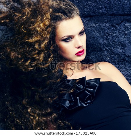 Portrait of a beautiful girl with flying hair. Girl with evening make-up and cocktail dress - stock photo