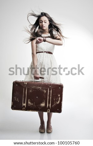 portrait of a beautiful girl with long and developing hair with a suitcase in his hand  on a white background - stock photo