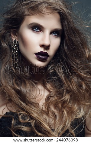 Portrait of a beautiful girl with long curly hair in the studio in the Gothic style