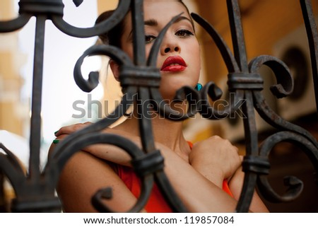 Portrait of a beautiful girl with professional make-up, posing in the city next to the vintage gate - stock photo