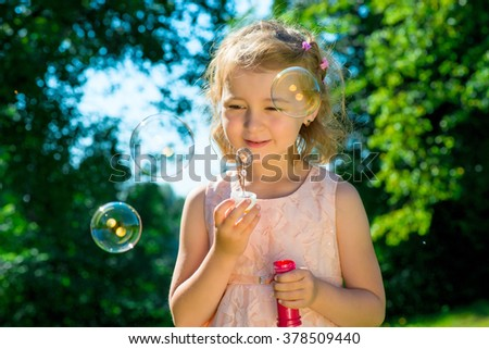 portrait of a beautiful girl with soap bubbles - stock photo