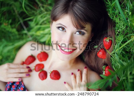 portrait of a beautiful girl with strawberries in the park. - stock photo