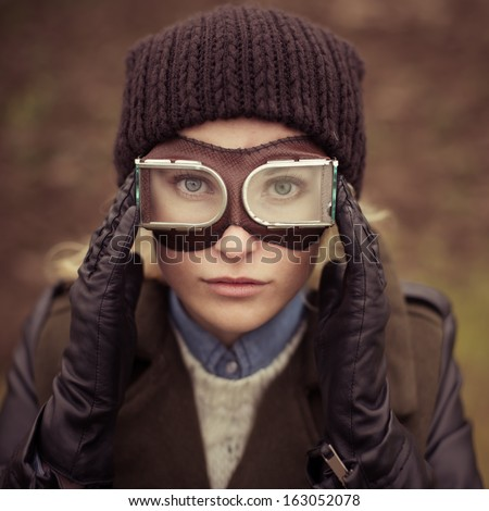 Portrait of a beautiful girl with the ideal face in the form of a vintage aviator - stock photo