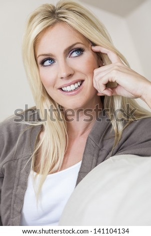 Portrait of a beautiful happy blond woman with blue eyes smiling and looking up - stock photo