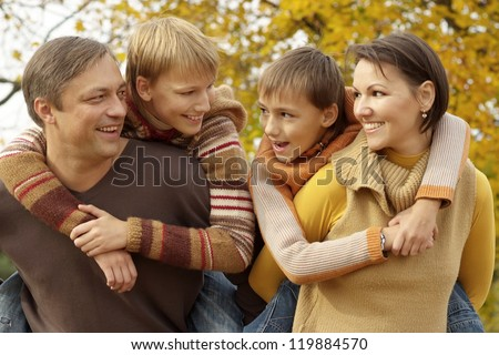 portrait of a beautiful happy family relaxing in autumn - stock photo
