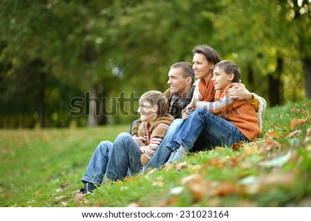 Portrait of a beautiful happy family sitting in autumn park
