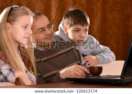 portrait of a beautiful happy family with a laptop on a brown - stock photo