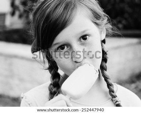 portrait of a beautiful happy girl eating ice cream - stock photo