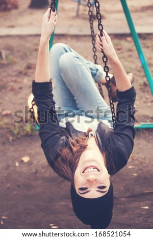 Portrait of a beautiful happy girl hipster on a swing. Outdoors. - stock photo