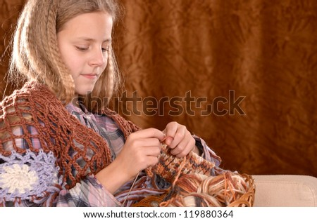 portrait of a beautiful happy girl knits on a brown background - stock photo