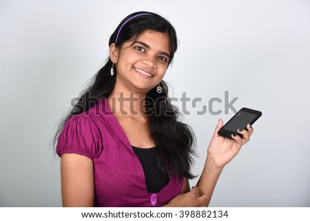 Portrait of a beautiful happy girl using her phone to text message isolated on grey background