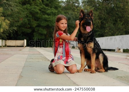 Portrait of a beautiful happy little girl with a puppy German shepherd outdoors - stock photo