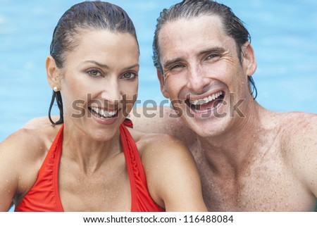 Portrait of a beautiful happy man and woman couple laughing in a swimming pool smiling with perfect teeth.