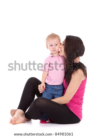Portrait of a beautiful happy mother kiss child 2 years boy isolated on white - stock photo