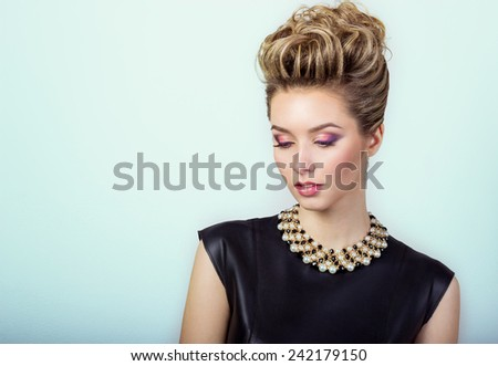 portrait of a beautiful happy sexy young woman smiling in a black evening dress with hair and make-up with expensive jewelry in Studio on white background - stock photo