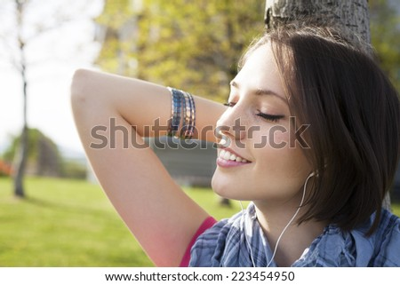 Portrait of a beautiful happy young woman sitting on grass, enjoy sunny day and listening music with headphones. - stock photo