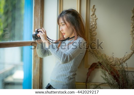 portrait of a beautiful hipster girl with a camera taking photos