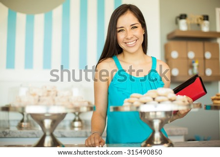 Portrait of a beautiful Hispanic customer buying some cookies in a cake shop and smiling