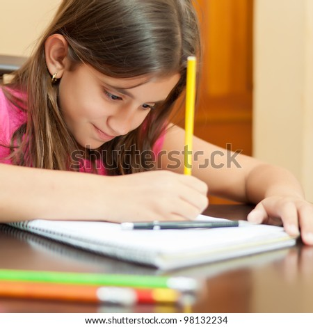 Portrait of a beautiful hispanic girl working on her art project at home - stock photo