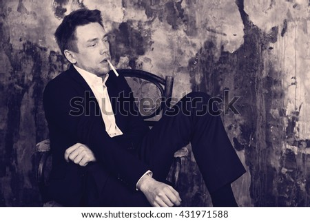 Portrait of a beautiful imposing man with cigarette on vintage wall background. Sits on vintage chair. Blond. Dressed in a classic formal suit. Antique colour graded.