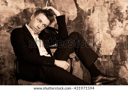 Portrait of a beautiful imposing man with cigarette on vintage wall background. Sits on vintage chair. Blond. Dressed in a classic formal suit.  Sepia colour graded.