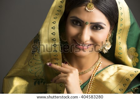 Portrait of a beautiful Indian woman in traditional sari and jewelry with makeup on dark background. - stock photo