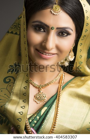 Portrait of a beautiful Indian woman in traditional sari and jewelry with makeup on dark background.