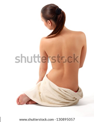 Portrait of a beautiful lady covering herself with a white towel, isolated on white