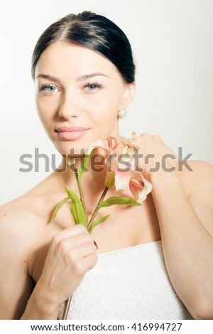 Portrait of a beautiful lady looking at camera face with red lipstick and lilies flower. Perfect skin.