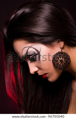 Portrait of a beautiful lady with art makeup - stock photo