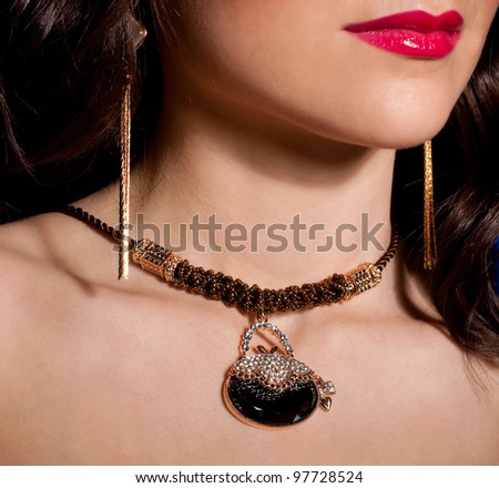 Portrait of a beautiful lady with golden jewelry - stock photo