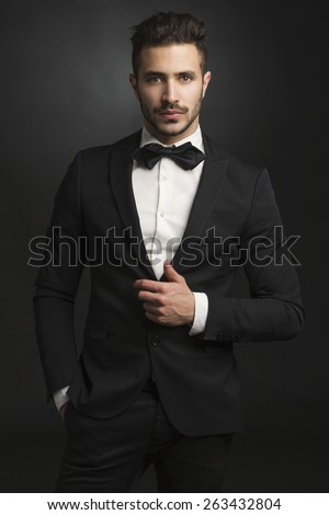 Portrait of a beautiful latin man smiling wearing a tuxedo - stock photo