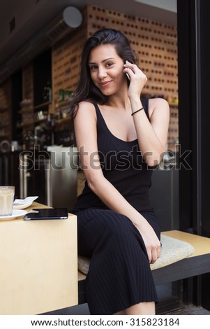 Portrait of a beautiful latin woman looking at the camera during telephone conversation, female student talking on her smart phone while resting after lectures in modern coffee shop in the fresh air - stock photo