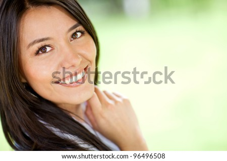 Portrait of a beautiful Latin woman smiling - outdoors - stock photo