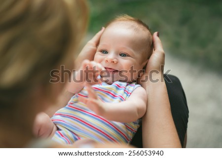 Portrait of a beautiful, laughing baby boy with gorgeous blue eyes being held by his mother, on his back, in her lap in the garden - stock photo