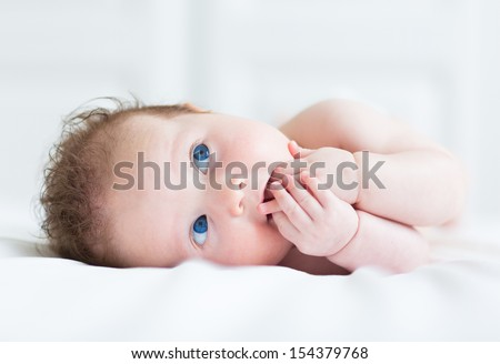 Portrait of a beautiful little baby with big blue eyes sucking on her finger - stock photo